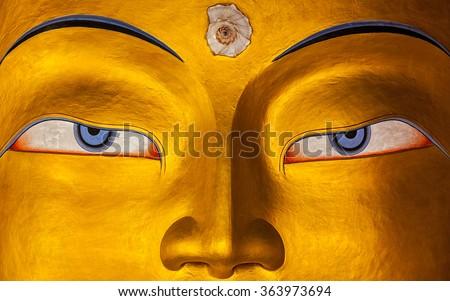 Eyes of Maitreya Buddha face close up. Thiksey Gompa. Ladakh, India - stock photo