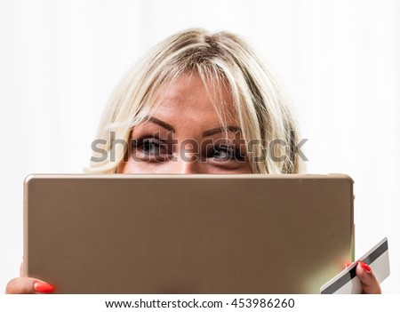 Eyes of woman looking sideways with tablet computer and credit card between fingers in front of bright windows