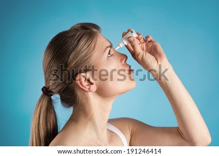 Eyes pain treatment. POrtrait of young woman using eye drops over blue background.   - stock photo