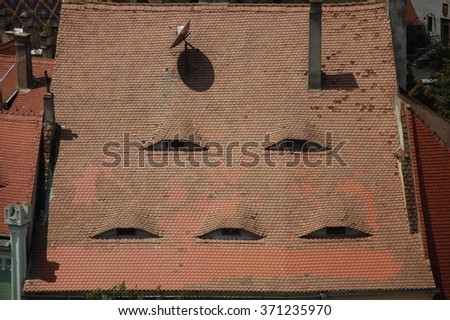 Eyes that stare. Typical roof of a home in Sibiu, Romania. - stock photo