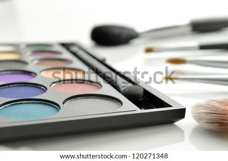 Eyeshadow palette and makeup brushes on white background. - stock photo