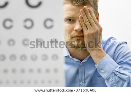 eyesight check. male patient under eye vision examination - stock photo