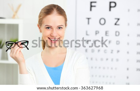 eyesight check. woman with  glasses at the doctor ophthalmologist optician - stock photo