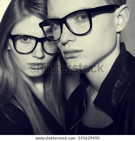 Eyewear concept. Family portrait of gorgeous blond fashion twins in black clothes wearing trendy glasses and posing over gray background together. Perfect skin. Vogue style. Close up. Studio shot - stock photo