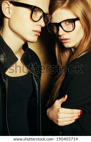 Eyewear concept. Family portrait of gorgeous blond fashion twins in black clothes wearing trendy glasses and posing over golden background together. Perfect skin. Vogue style. Studio shot - stock photo