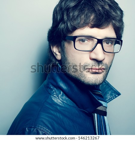 Eyewear concept. Portrait of a fashionable handsome man in trendy glasses, blue jacket with striped scarf over light blue background. Urban hipster style. Close up. Studio shot