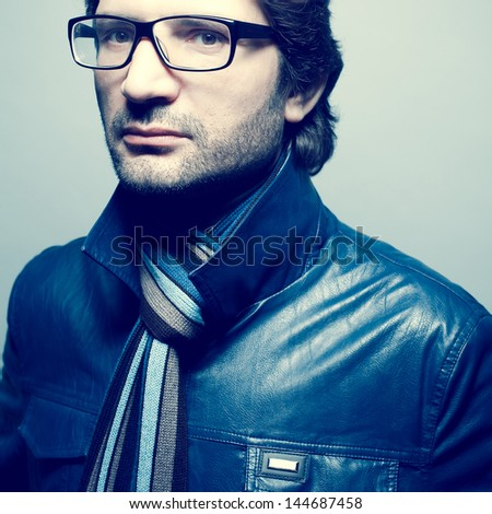 Eyewear concept. Portrait of a fashionable handsome mature man in blue leather jacket with striped scarf posing over light blue background. Hipster style. Close up. Studio shot