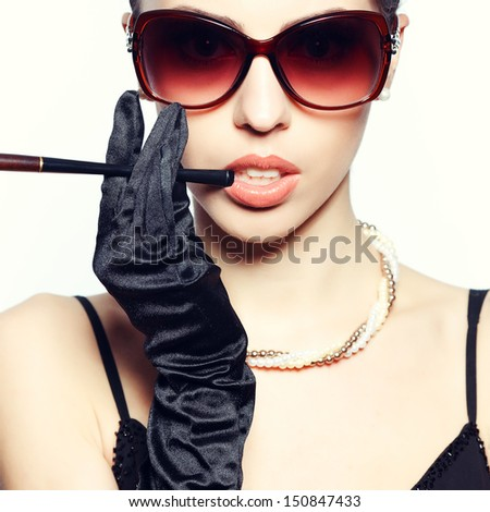 Eyewear concept. Portrait of a fashionable model in vintage sunglasses with a cigarette holder. Perfect skin. Great pearl accessories. Retro style. Close up. Studio shot