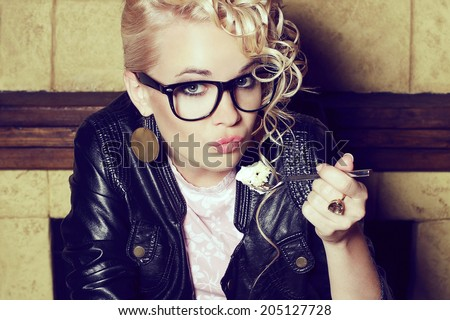 Eyewear concept. Portrait of a funny hipster blonde girl with great hairdo in trendy glasses and black leather jacket eating cake in vintage restaurant. Duck face emotion. Close up. Indoor shot
