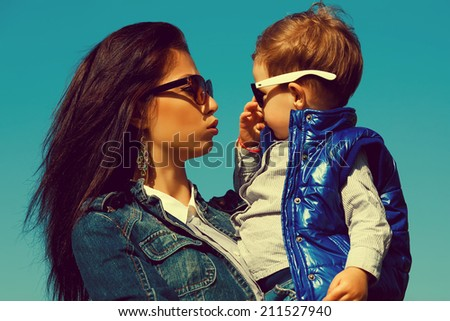 Eyewear concept. Portrait of fashionable baby boy & his gorgeous mother (hollywood star) in trendy sunglasses walking in the street. Son crying. Sunny spring day. Outdoor shot