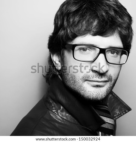 Eyewear concept. Portrait of fashionable handsome mature man in leather jacket with striped scarf posing over gray background. Vogue style. Close up. Copy-space. Black & white (monochrome) studio shot - stock photo
