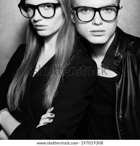 Eyewear concept. Portrait of gorgeous fashion twins in black clothes wearing trendy glasses and posing over metal background together. Perfect hair and skin. Natural make-up. Studio shot - stock photo