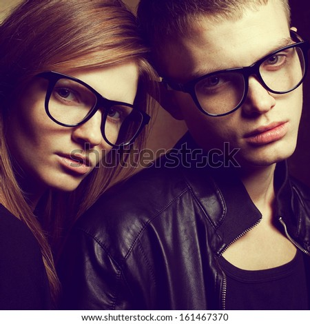 Eyewear concept. Portrait of gorgeous red-haired fashion twins in black leather clothes wearing trendy glasses and posing over golden background together. Hipster style. Close up. Studio shot - stock photo