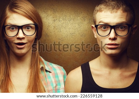 Eyewear concept. Portrait of gorgeous red-haired twins in casual shirts wearing trendy glasses and posing over golden background together with wow faces (duck-face). Hipster style. Studio shot - stock photo