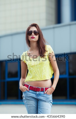 Eyewear concept. Portrait of gorgeous young woman in handmade knitted top, blue jeans, aviator type sunglasses posing in the street. Hands in pockets. Urban  casual style. Outdoor shot