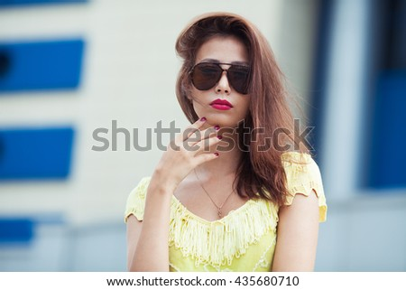 Eyewear concept. Portrait of gorgeous young woman in yellow-green handmade knitted top, aviator type sunglasses, posing in the street. Urban style. Copy-space. Close up. Outdoor shot
