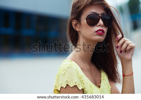 Eyewear concept. Portrait of gorgeous young woman in yellow-green handmade knitted top, aviator type sunglasses, posing in the street. Urban style. Copy-space. Close up. Outdoor shot - stock photo