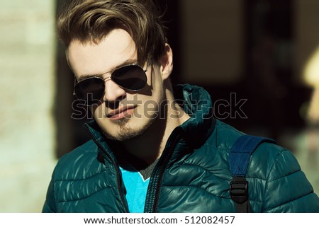 Eyewear concept. Portrait of handsome young man with short blond hair wearing blue sport style jacket, walking in he city. Close up. Copy-space. Outdoor shot