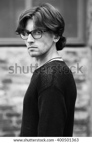 Eyewear concept. Portrait of romantic charismatic man wearing stylish eyeglasses. Close up. Urban, street style. Monochrome, black and white outdoor shot.