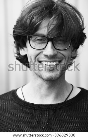 Eyewear concept. Portrait of romantic charismatic smiling man wearing stylish eyeglasses. Close up. Monochrome, black and white outdoor shot. - stock photo