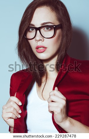 Eyewear concept. Portrait of young beautiful student girl wearing trendy glasses, casual clothing and posing over light blue background. Perfect skin ad make up. Hipster style. Close up. Studio shot - stock photo