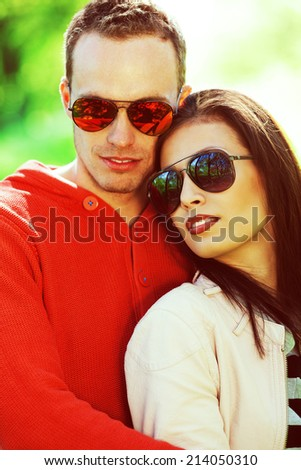 Eyewear concept. Smiling young woman and her boyfriend in trendy sunglasses posing in the park. Stylish casual clothing. White shiny smiles. Spring (autumn) sunny weather. Close up. Outdoor shot - stock photo