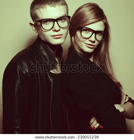 Eyewear & hipster squad concept. Portrait of red-haired twins in black clothes wearing trendy glasses and posing over beige background together. Perfect hair, skin. Natural make-up. Studio shot