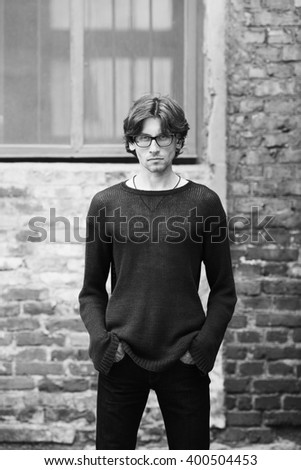 Eyewear, street fashion concept. Portrait of romantic charismatic man wearing stylish eyeglasses. Monochrome, black and white outdoor shot.