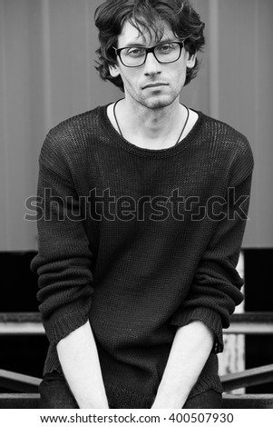 Eyewear, street fashion concept. Portrait of romantic charismatic man wearing stylish eyeglasses. Monochrome, black and white outdoor shot. - stock photo