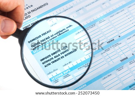 F24 for the tax return in Italy with magnifying glass. - stock photo