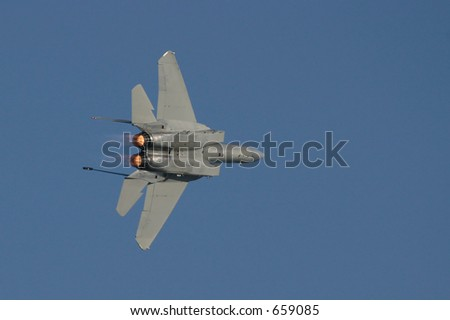 F-15 in flight in banking turn with afterburner flames visible