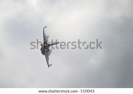 F-16 jet in a hard banking turn with afterburner lit.  Vapor clouds forming over the wings as it rips through the air - stock photo