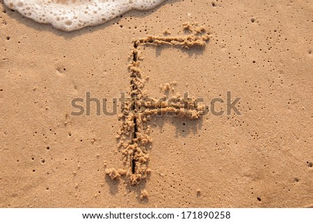 F text written in the sandy on the beach - stock photo