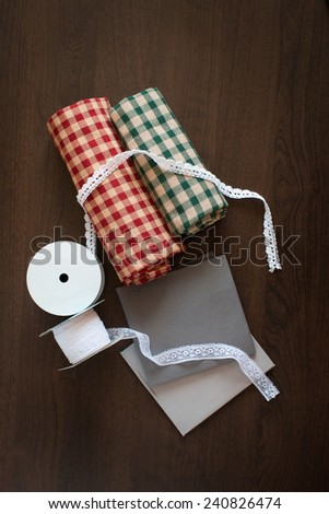 Fabric and ribbon on wooden table - stock photo