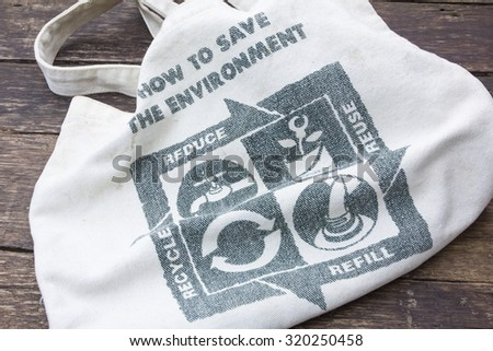 Fabric eco bag with recycle sign icon made of green leaf, on a wooden background - stock photo