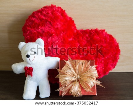 Fabric fluffy red heart shape on wooden table and white bear, red gift box, valentine concept