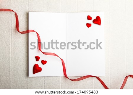 Fabric hearts on an empty opened postcard and a red ribbon on textured background. Valentine Day design.