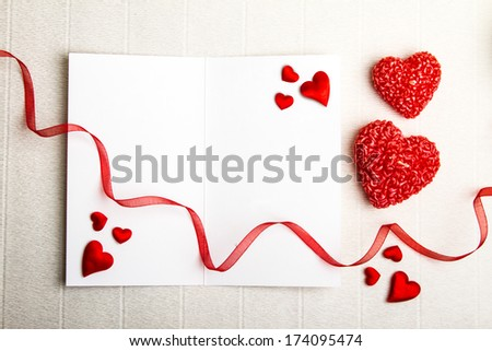 Fabric hearts on an empty opened postcard with two heart-shaped candles and a red ribbon on textured background. Valentine Day design.