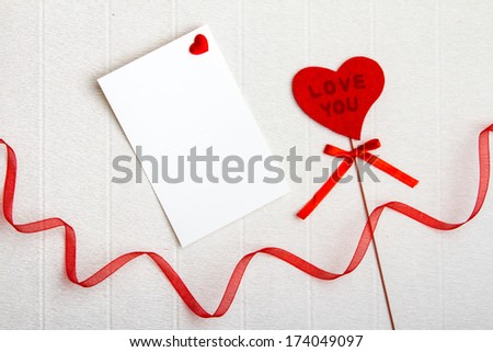 Fabric Love You heart with an empty postcard and a red ribbon on