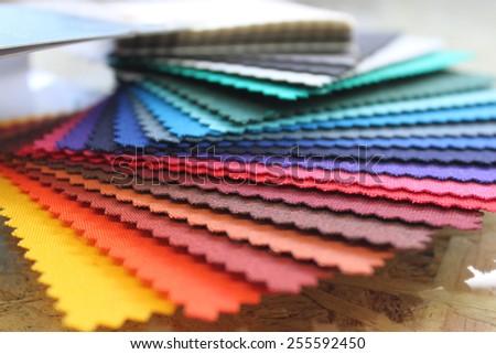 Fabric rainbow color swatch book - stock photo