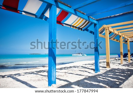 Fabric roof in wood protection from the sun and sunlight where sun loungers and on the beautiful cuban beach of Varadero with a clear blue sky - stock photo