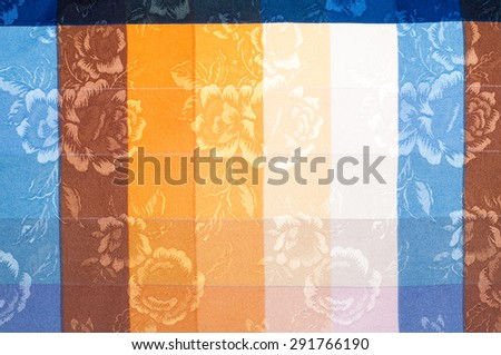 fabric texture silk. background. Vertical lines. Blue red brown yellow white stripe. embroidered flowers. - stock photo