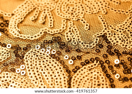 Fabric with bright sequins for background. Closeup of fabric embroidered with sequins.