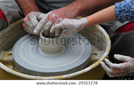 fabrication of the crockery on potter's wheel by pupil with teacher