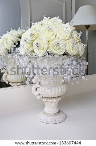 Fabulous bouquet of white roses and shining crystals in ancient ceramic vase, standing in front of the mirror in luxury residence. Wedding decoration.