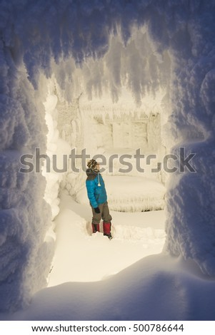 Fabulous house with frost and snow on the walls. Man standing in snowdrift and look at the beautiful room. Christmas holidays in an interesting place