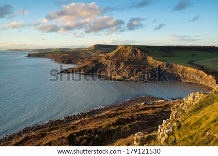 Fabulous late afternoon view across Chapman's Pool with the sun reflecting off the face of Houns-tout Cliff. Dorset, UK. Part of Dorset's Jurassic coastline, a UNESCO world heritage site