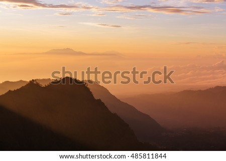 Fabulous light of sun rays at beautiful sunrise in mountains of Java island, Indonesia