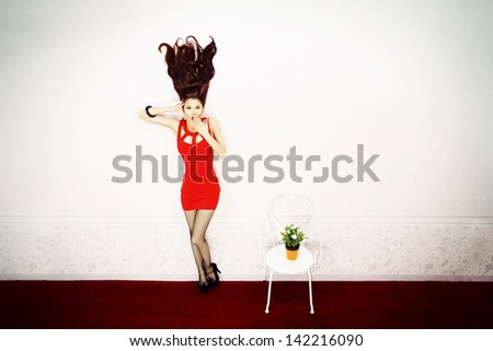 Fabulous young woman with flying up hair standing in a pink room.