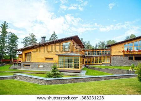 Facade of a beautiful wooden house with green garden - stock photo